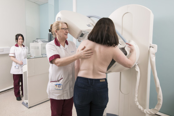 Healthcare professor guiding female patient during her mammogram