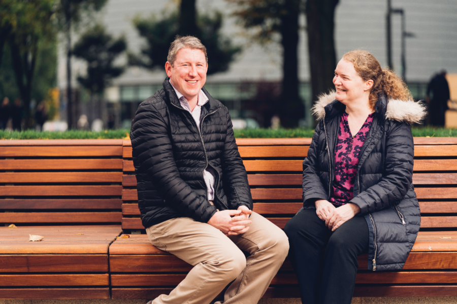 Dr Phil Crosbie, looking at camera smiling and sitting on a bench. Next to him sits Professor Emma Crosbie, smiling and looking at him.