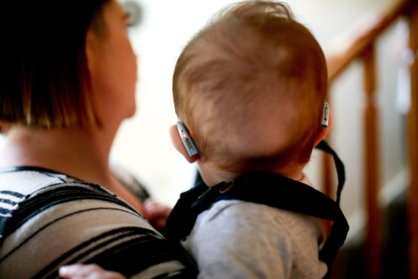 Mother holding baby with hearing aids